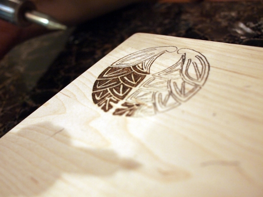 First you draw your design onto the wood using the transfer paper, then go over it with the pyrography pen.